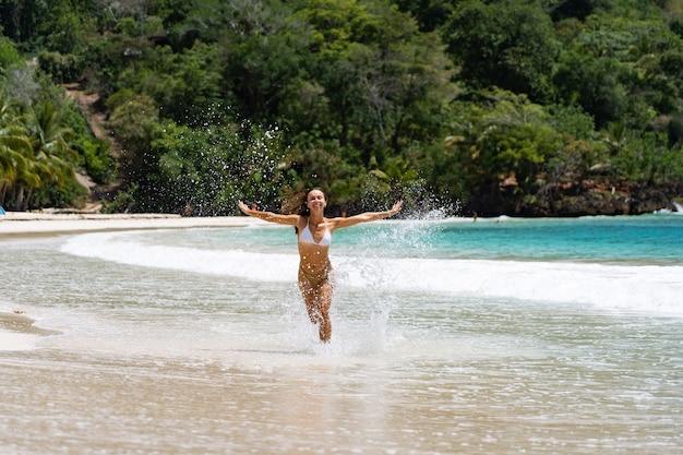Młoda radosna kobieta w stroju kąpielowym szczęśliwie działa na plaży. koncepcja wakacji i podróży.