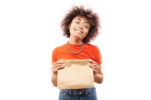 Młoda radosna kobieta z lokami afro w pomarańczowych ubraniach trzymających pakiet rzemieślniczy na białym tle studia, dostawa żywności, torba ekologiczna, kazachska kaukaska dziewczyna z prezentem