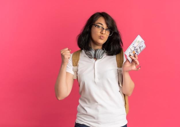 Młoda radosna, ładna kaukaska uczennica ze słuchawkami na szyi w okularach i torbie z tyłu trzyma pieniądze i podnosi rękę na różowo z miejscem na kopię