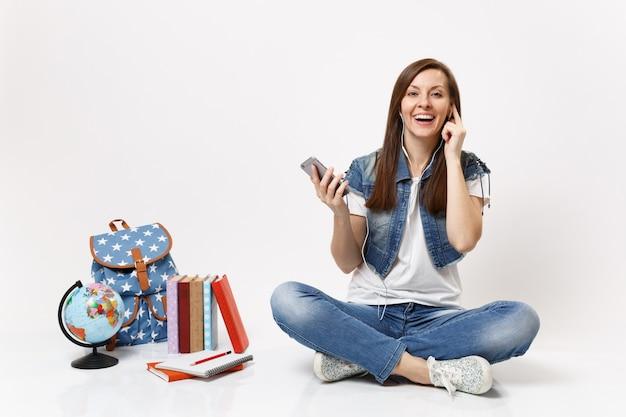 Młoda radosna ładna kobieta uczennica ze słuchawkami słuchająca muzyki trzymająca telefon komórkowy siedząca w pobliżu globusa plecak szkolna książka na białym tle