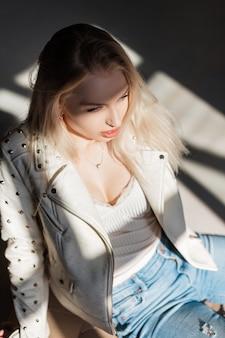 Młoda radosna piękna blond kobieta w modnej beżowej skórzanej kurtce z nitami w stylowej koszulce w niebieskich dżinsach siedzi w pomieszczeniu w jasny słoneczny dzień