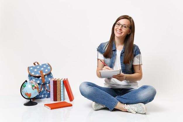 Młoda radosna piękna studentka w okularach pisząca notatki na notebooku siedząca w pobliżu kuli ziemskiej, plecaka, podręczników szkolnych na białym tle