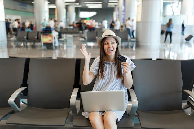 Młoda radosna podróżniczka turystyczna kobieta pracująca na laptopie trzymaj kartę kredytową rozkładając ręce, czekaj w holu na międzynarodowym lotnisku