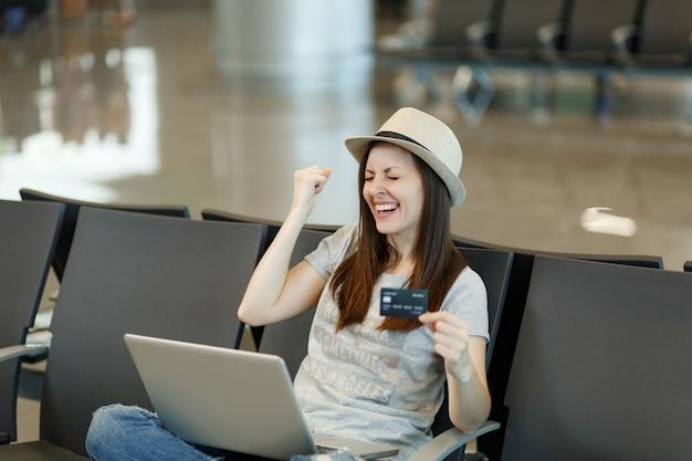 Młoda radosna podróżniczka turystyczna siedząca na laptopie, wykonująca gest zwycięzcy, trzymająca kartę kredytową, czekająca w holu na lotnisku