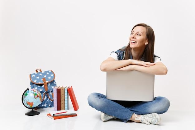 Młoda radosna roześmiana studentka opierając się na laptopie, patrząc na bok, siedząc w pobliżu kuli ziemskiej, plecaka, podręczników szkolnych na białym tle