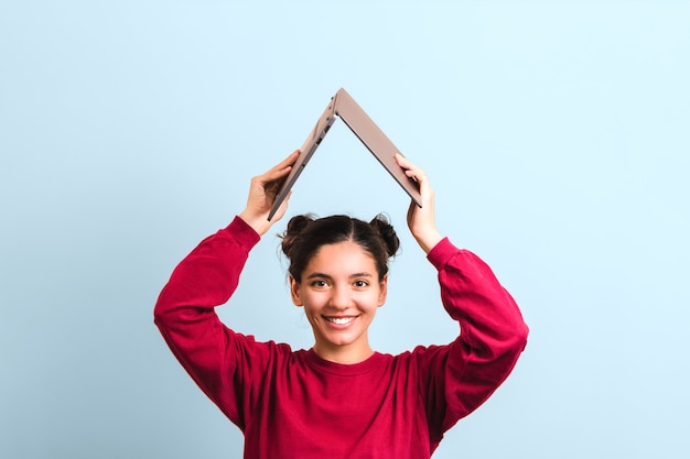 Młoda radosna studentka kobieta z pięknym uśmiechem trzyma otwarty laptop nad głową w postaci dachu.