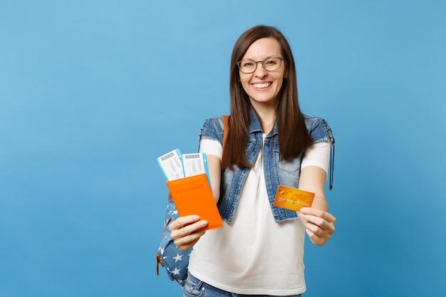 Młoda radosna szczęśliwa kobieta studentka w okularach z plecakiem trzymać paszport karta pokładowa bilet karta kredytowa na białym tle na niebieskim tle. kształcenie na uczelniach wyższych za granicą. koncepcja lotu podróży lotniczych.