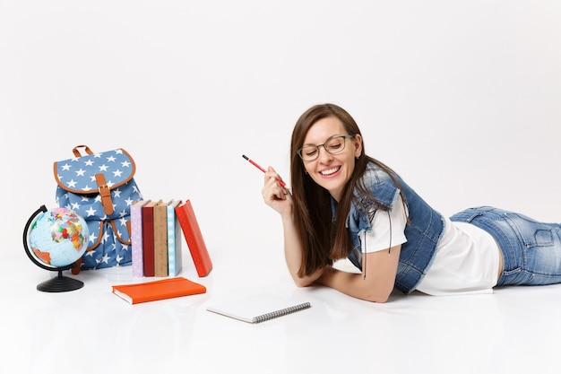 Młoda radosna szczęśliwa studentka w dżinsowych ubraniach, okulary trzymające ołówkowy notatnik leżący w pobliżu kuli ziemskiej, plecak, podręczniki szkolne na białym tle