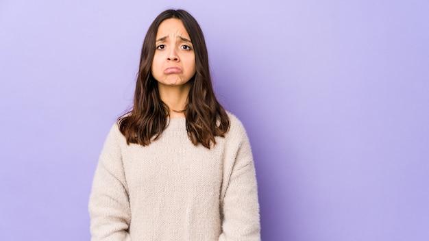 Młoda rasa mieszana hiszpanin kobieta na białym tle dmucha w policzki, ma zmęczony wyraz