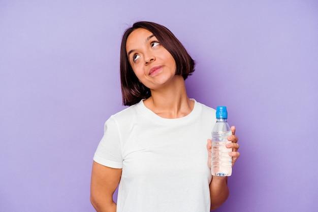 Młoda rasa mieszana trzyma butelkę wody na białym tle na fioletowym tle marzy o osiągnięciu celów i zamierzeń