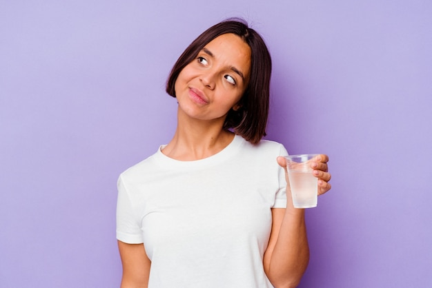 Młoda rasa mieszana trzyma szklankę wody na białym tle na fioletowym tle marzy o osiągnięciu celów i zamierzeń
