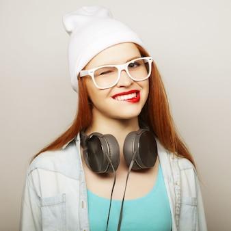 Młoda redhair kobieta słucha muzykę z hełmofonami.