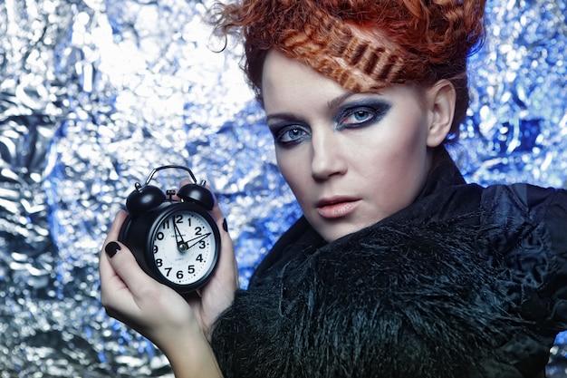Młoda redhair kobieta z zegarem