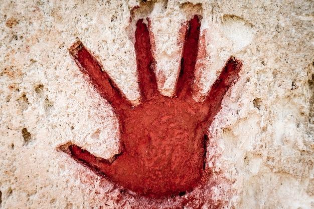 Młoda ręka malowana na czerwono na kamieniu - graficzny element gotycki