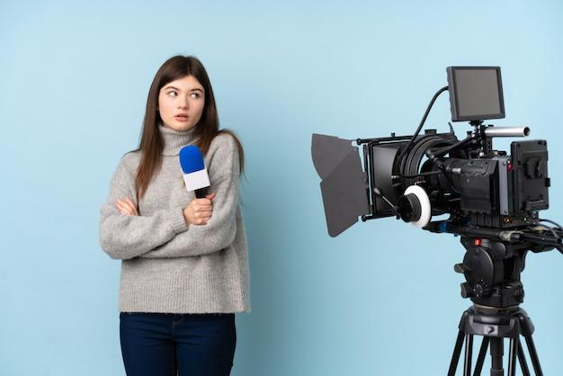 Młoda reporter kobieta trzyma mikrofon i donosi wiadomości myśleć pomysł