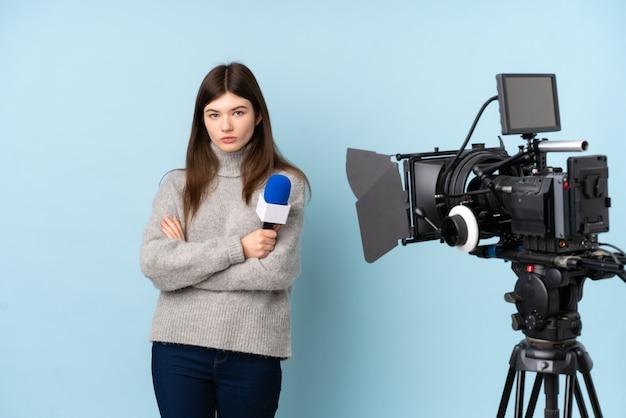 Młoda reporter kobieta trzyma mikrofon i donosi wiadomości utrzymanie rękami skrzyżowanymi