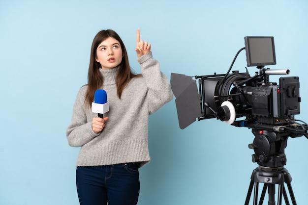 Młoda reporter kobieta trzyma mikrofon i reportaż dotyka na przejrzystym ekranie