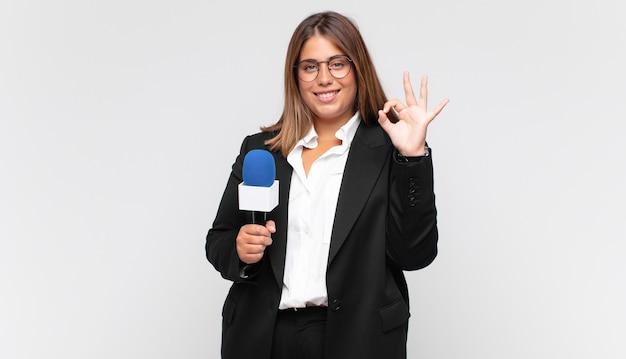 Młoda reporterka czuje się szczęśliwa, odprężona i usatysfakcjonowana, okazując aprobatę dobrym gestem, uśmiechając się