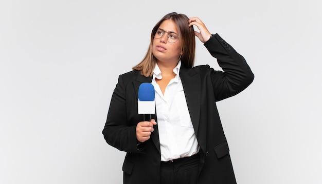 Młoda reporterka czuje się zdziwiona i zdezorientowana, drapiąc się po głowie i patrząc w bok