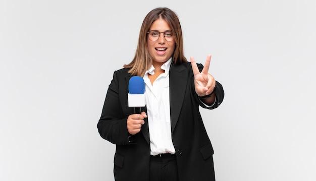 Młoda reporterka uśmiechnięta i wyglądająca na szczęśliwą, beztroską i pozytywną, gestykulującą jedną ręką zwycięstwo lub pokój