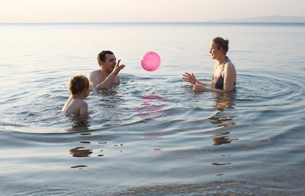 Młoda rodzina bawić się z piłką przy zmierzchem