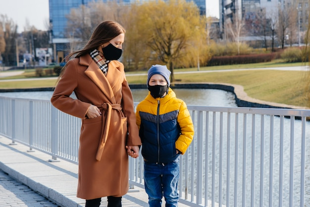 Młoda rodzina chodzi i oddycha świeżym powietrzem w słoneczny dzień podczas kwarantanny i pandemii. maski na twarzach ludzi