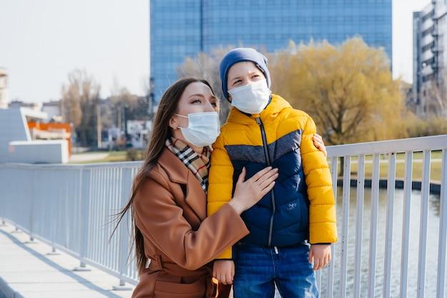 Młoda rodzina chodzi i oddycha świeżym powietrzem w słoneczny dzień podczas kwarantanny i pandemii. maski na twarzach ludzi.