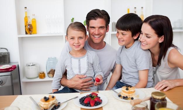 Młoda rodzina jedzenia owoców i naleśniki na śniadanie