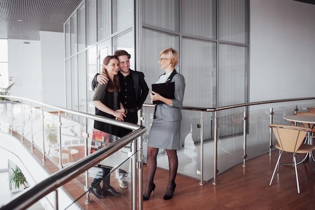 Młoda rodzina komunikuje się z urzędnikiem przez kobietę w korytarzu biurowym