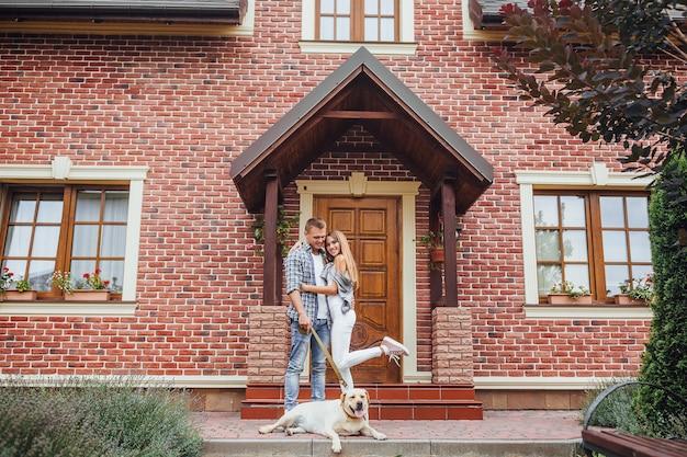 Młoda rodzina kupiła nowy dom. atrakcyjni mężczyźni i kobieta z labradorem w pobliżu dużego domu. para patrząc w kamerę.