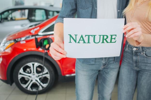 Młoda rodzina kupuje pierwszy samochód elektryczny w salonie. zielony samochód. zbliżenie: trzymając się za ręce papier ze słowem nature na tle samochodu elektrycznego baterii. ochrona środowiska.