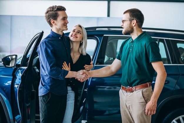 Młoda rodzina kupuje samochód w samochodowej sala wystawowej