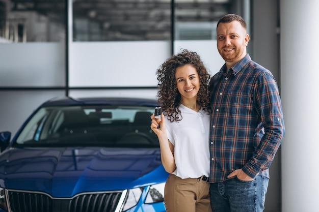 Młoda rodzina kupuje samochód w samochodowym salonie wystawowym