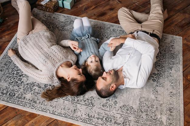 Młoda rodzina, leżąc na podłodze w domu w ubranie