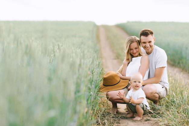 Młoda rodzina ma dobrą zabawę z małym dzieckiem na polu