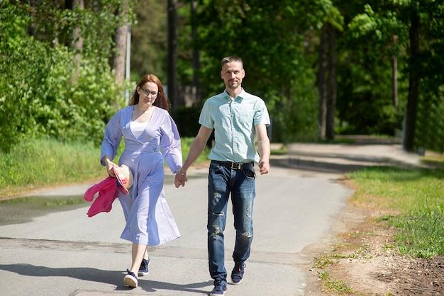 Młoda rodzina, małżeństwo, mężczyzna i kobieta spaceru w parku w słoneczny letni dzień