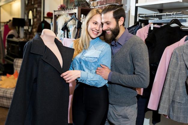 Młoda rodzina, mężczyzna i kobieta przytulają się i wybierają czarny płaszcz w sklepie odzieżowym.