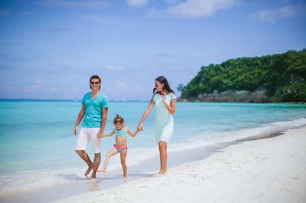 Młoda rodzina na białej plaży podczas letnich wakacji