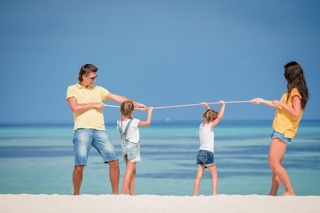 Młoda rodzina na wakacjach świetnie się razem bawi. rodzice i dzieci bawią się razem