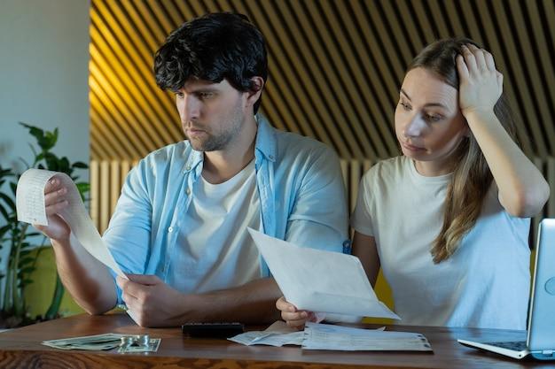 Młoda rodzina robi papierkową robotę w domu młoda para szuka zmartwiony siedząc przy stole z dużą ilością dokumentów papierowych