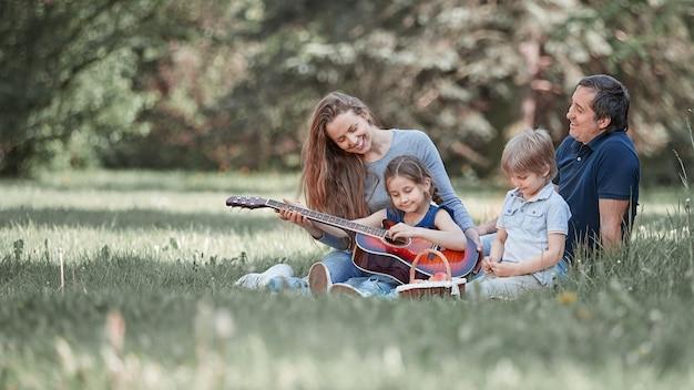 Młoda rodzina siedzi na trawie w letnim parku