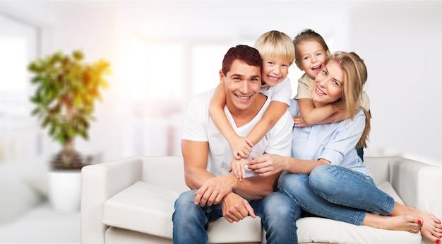 Młoda rodzina siedzi w domu na kanapie obejmując się i uśmiechając