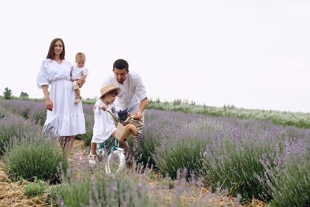 Młoda rodzina spaceruje z dziećmi po lawendowym polu.