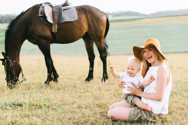 Młoda rodzina świetnie się bawi w terenie. rodzice i dziecko z koniem