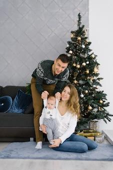 Młoda rodzina świętuje boże narodzenie w domu w salonie obok choinki. szczęśliwa mama, tata i syn spędzają razem wakacje. wesołych świąt i wesołych świąt!