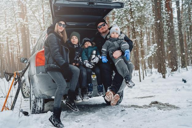 Młoda rodzina ubrana w ciepłą odzież stanowią na aparacie, siedząc na bagażniku samochodu w zimowym lesie w ciągu dnia.