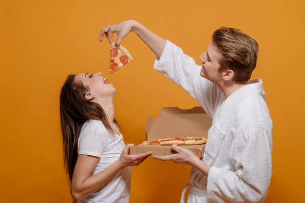Młoda rodzina w domowych ubraniach w kwarantannie z włoską pizzą pepperoni, karmi się nawzajem, dobre relacje rodzinne, śmieszny rodzinny pojęcie