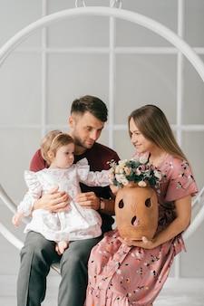 Młoda rodzina w jasnym pokoju ze swoją śliczną córeczką siedzą na huśtawce i cieszą się rozrywką.