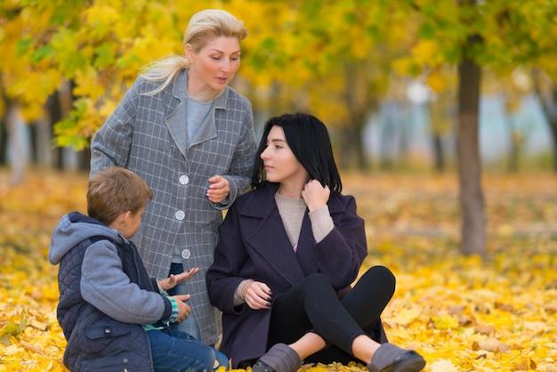 Młoda rodzina w jesiennym parku siedzi na czacie na ziemi wśród kolorowych żółtych liści jesienią w lesie z drzewami