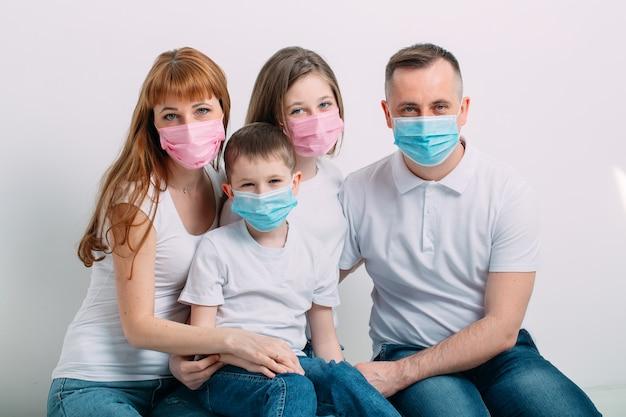 Młoda rodzina w medycznych maskach podczas domowej kwarantanny.